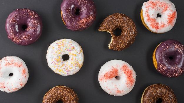 Conjunto de deliciosos donuts mordidos doces com revestimento colorido Foto gratuita