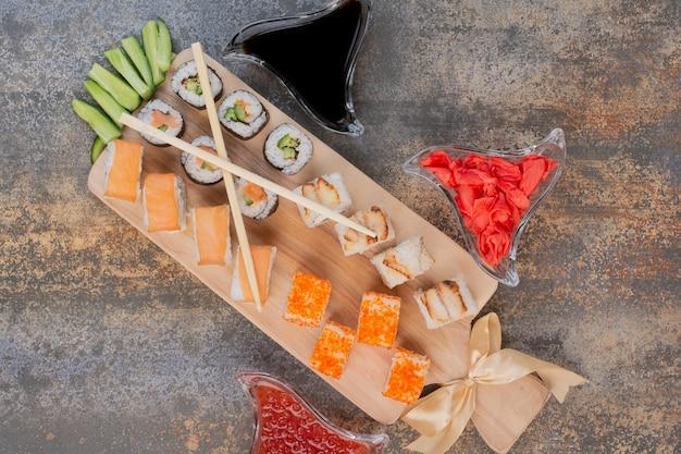 Conjunto de deliciosos sushis com pauzinhos e gengibre em superfície de mármore Foto gratuita