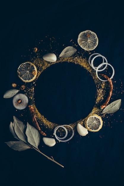 Conjunto de especiarias: limão, cebola, pimenta, pimentão, louros, erva-doce, endro isolado em fundo escuro. borda de quadro picante Foto Premium