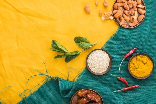 Conjunto de especiarias perto de plantas, frutos secos e nozes Foto gratuita