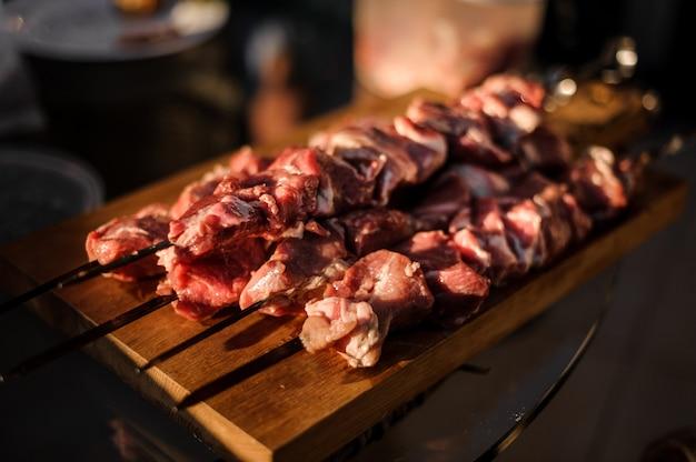 Conjunto de espetos com pedaços de carne fresca dispostos em cima da mesa de comida Foto Premium