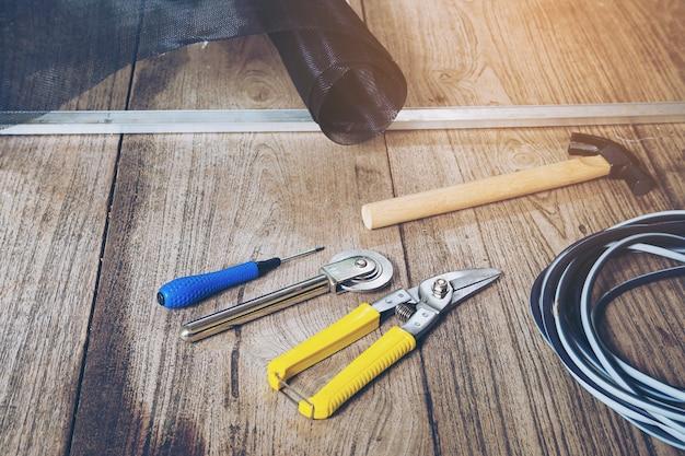 Conjunto de ferramentas manuais e tela de mosquito danificada que precisa ser consertada Foto gratuita