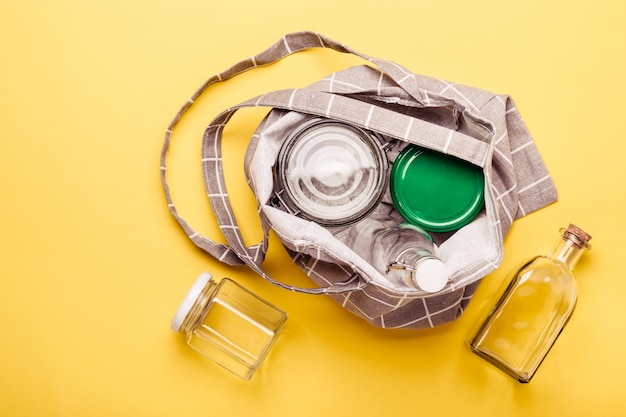 Conjunto de frascos e saco têxtil em fundo amarelo para zero desperdício de compras Foto Premium