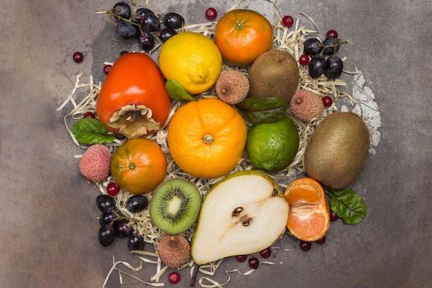 Conjunto de frutas exóticas variadas e multicoloridas. tangerinas, toranjas, lichias, kiwis e uvas com folhas de acelga. postura plana Foto Premium