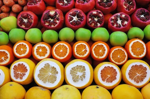 Conjunto de frutas no mercado de romãs e frutas cítricas Foto gratuita