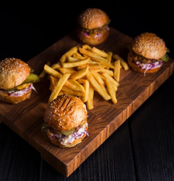 Conjunto de hambúrgueres clássicos com batatas fritas em uma placa de madeira Foto gratuita