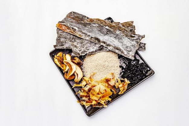 Conjunto de ingrediente tradicional japonês para cozinhar o caldo básico dashi. algas kombu e wakame, katsuobushi e cogumelos secos. isolado Foto Premium