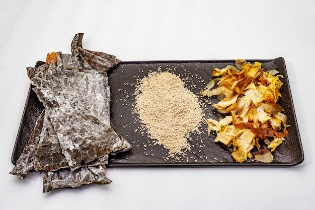 Conjunto de ingrediente tradicional japonês para cozinhar o caldo básico dashi. algas kombu, katsuobushi e grânulos secos acabados. isolado Foto Premium