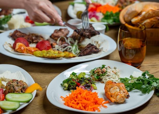 Conjunto de jantar em pratos brancos contendo carne e legumes, salgadinhos. Foto gratuita