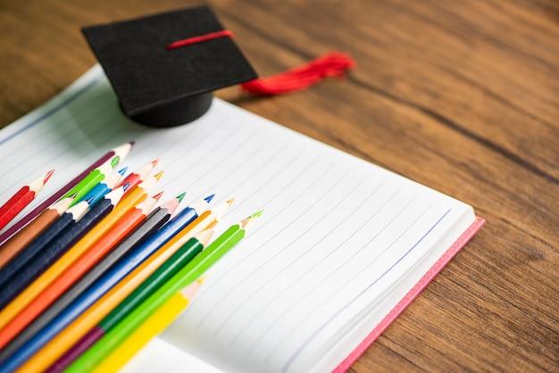 Conjunto de lápis de cor e chapéu de formatura em papel branco notebook de volta ao conceito de escola e educação - giz de cera colorido Foto Premium