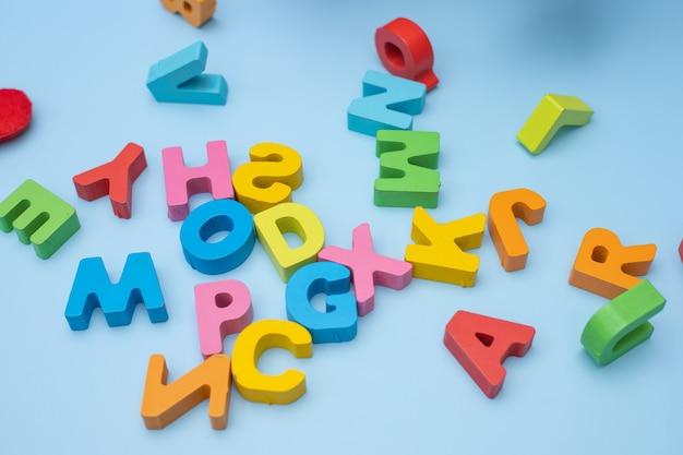 Conjunto de letras coloridas de madeira sobre fundo azul. vista do topo. Foto Premium