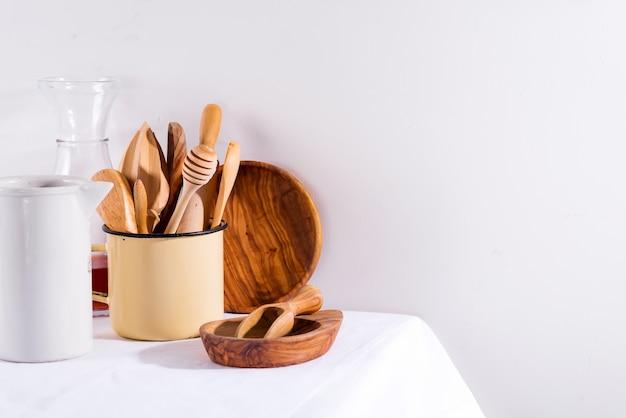 Conjunto de madeira de utensílios de cozinha em copo de ferro com placas de madeira na mesa branca de têxteis. aparelhos de cozinha. desperdício zero Foto Premium