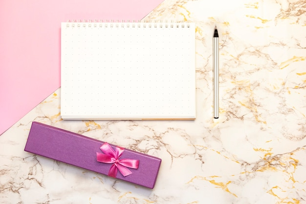 Conjunto de mesa de acessórios femininos - caderno com caneta, presentes de caixa, flor, vista superior Foto Premium
