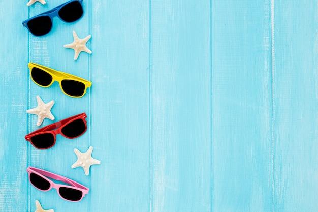 Conjunto de óculos de sol com estrelas do mar sobre fundo azul de madeira Foto gratuita