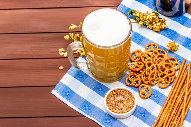 Conjunto de oktoberfest. cerveja light, pretzels, mostarda, palha de gergelim, lúpulo. Foto Premium