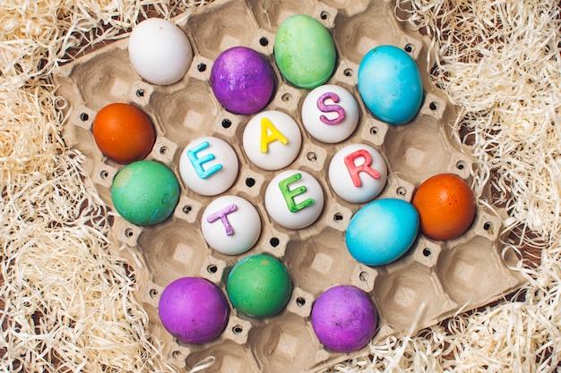 Conjunto de ovos brilhantes no recipiente com o título de páscoa entre ouropel Foto gratuita