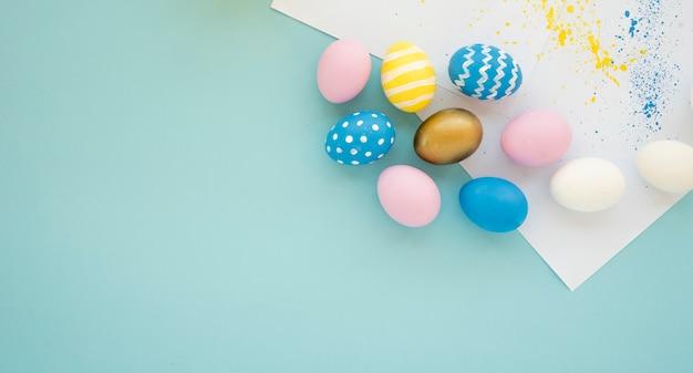 Conjunto de ovos brilhantes perto de papéis Foto gratuita