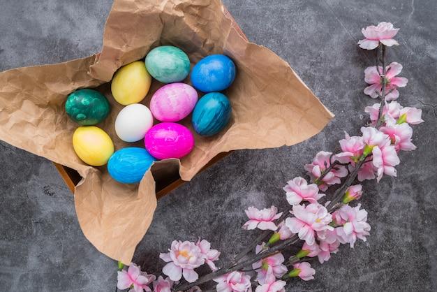 Conjunto de ovos de páscoa brilhantes em papel ofício em tigela perto de galho de flor Foto gratuita