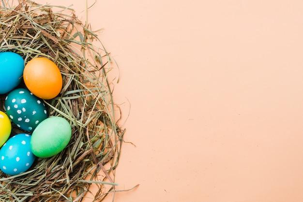 Conjunto de ovos de páscoa brilhantes no ninho Foto gratuita