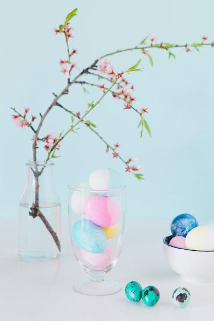 Conjunto de ovos de páscoa brilhantes perto de galho de flor em vaso com água e tigela Foto gratuita