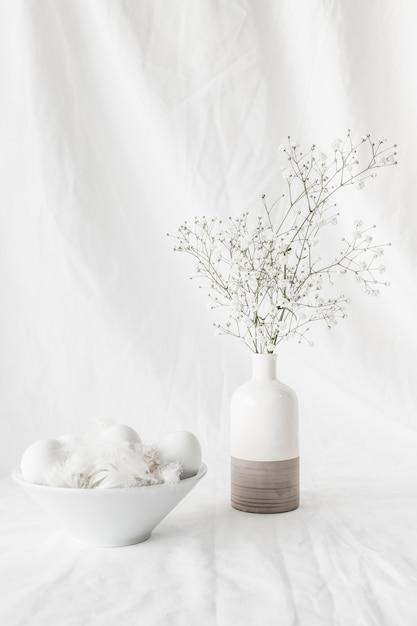 Conjunto de ovos de páscoa e penas na tigela perto de ramos de plantas em vaso Foto gratuita