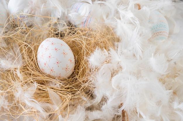 Conjunto de ovos de páscoa no feno entre montão de penas Foto gratuita