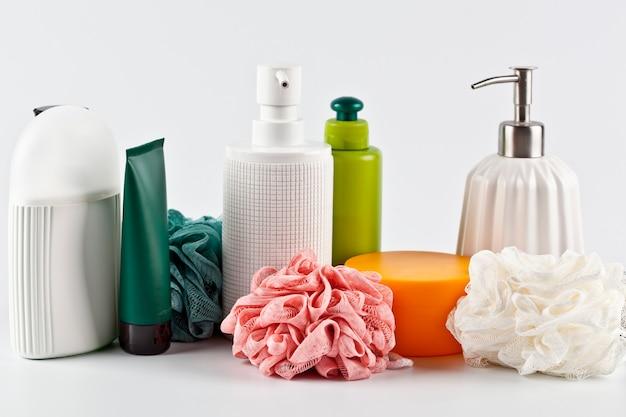 Conjunto de produtos cosméticos de banho e esponjas na superfície da luz. Foto Premium