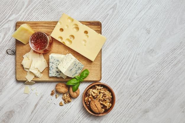 Conjunto de quatro queijos em uma tábua rústica isolada ao lado da mesa de madeira branca escovada. servido no café da manhã com mel rústico e nozes em uma tigela marrom com folhas de manjericão. vista do topo Foto gratuita