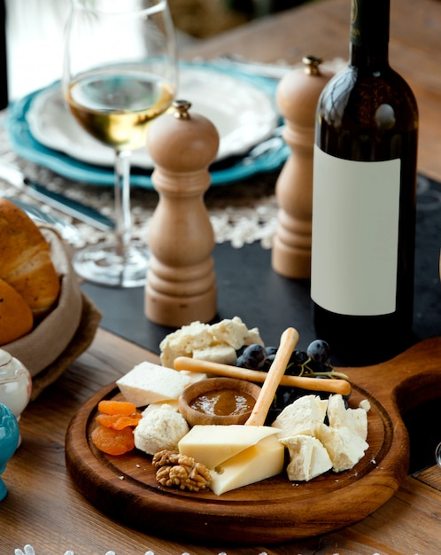 Conjunto de queijo com vinho tinto na placa de madeira Foto gratuita
