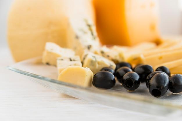 Conjunto de queijo fresco e azeitonas no prato Foto gratuita