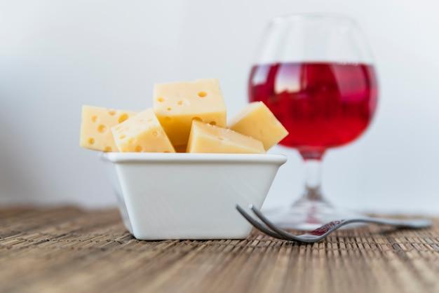 Conjunto de queijo fresco no prato perto de copo de bebida Foto gratuita