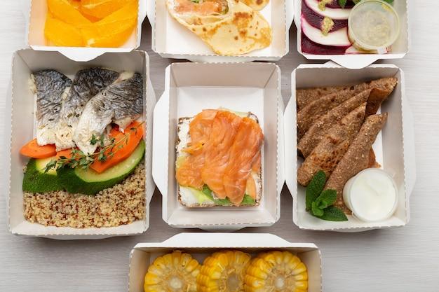 Conjunto de refeições saudáveis para o dia em lancheiras fica em uma mesa branca. Foto Premium