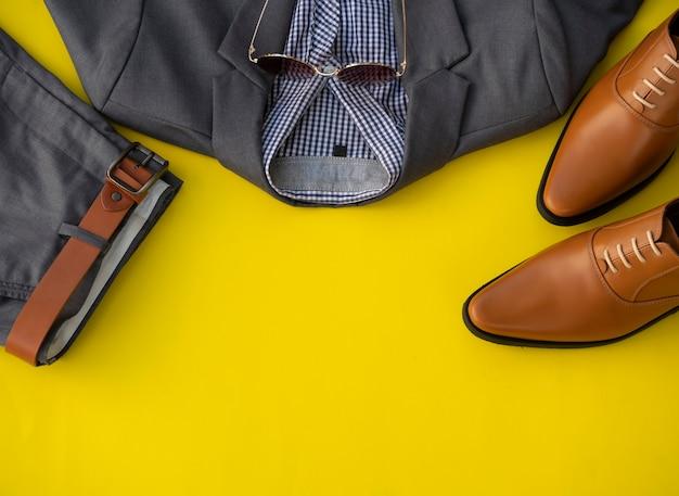 Conjunto de roupas de moda masculina e acessórios isolados em um fundo amarelo. conceito de roupas de homem de negócios Foto Premium