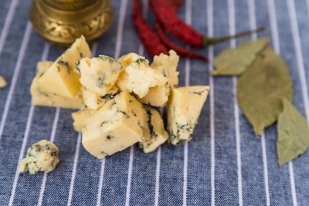 Conjunto de saboroso queijo azul perto de pimenta seca e folhas Foto gratuita