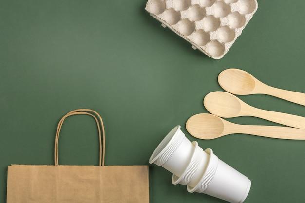 Conjunto de saco ecológico, xícaras de café de papel biodegradável, caixa de ovos de carrdboard, colheres de pau e garrafa de água de vidro. zero desperdício, ecológico, sem plástico. vista superior, copyspace. Foto Premium