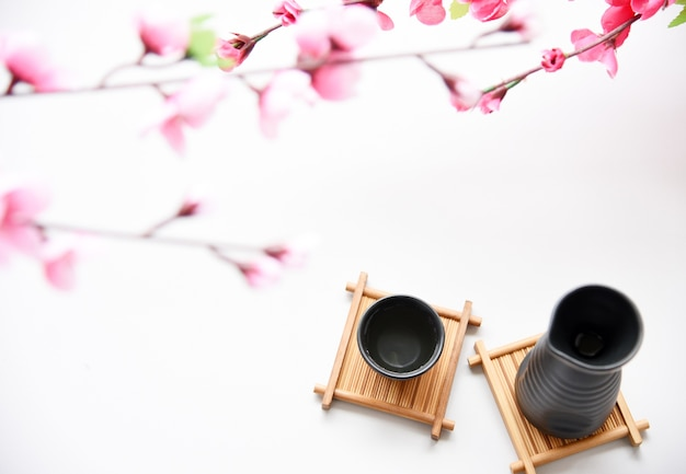 Conjunto de saquê japonês e flor sakura em fundo branco estilo de bebida oriental Foto Premium