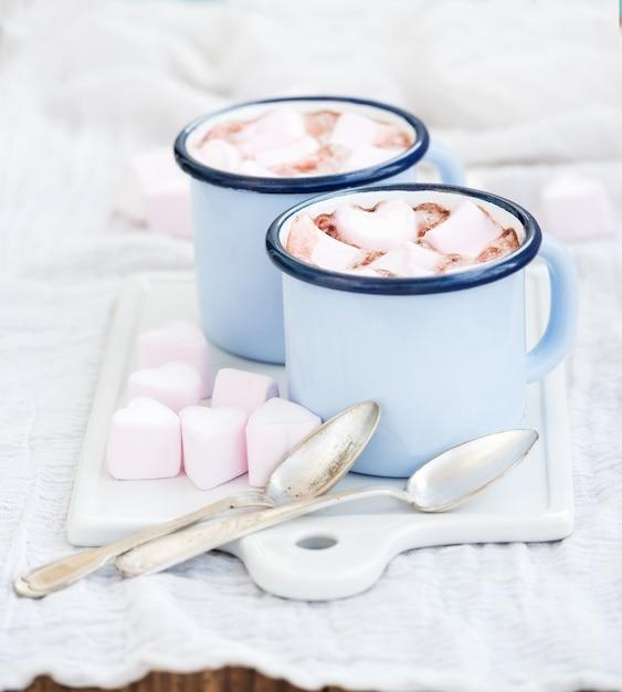 Conjunto de saudação do feriado dos namorados seint. chocolate quente e marshmallows em forma de coração em canecas de esmalte velhas na placa de servir de cerâmica branca Foto Premium