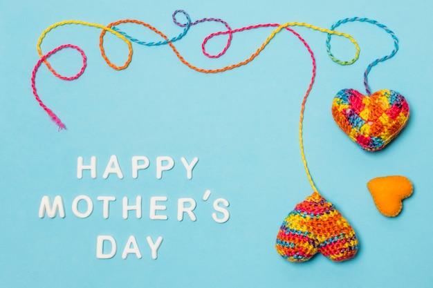 Conjunto de símbolos decorativos de coração perto de inscrição feliz dia das mães Foto gratuita