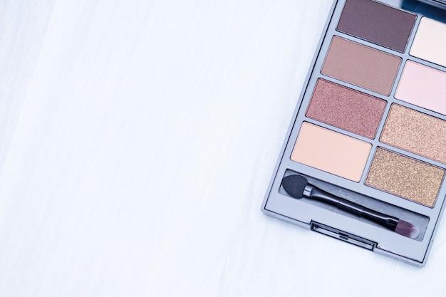 Conjunto de sombras de cosméticos para maquiagem. compõem os fundamentos nus, sobre fundo branco de madeira. postura plana, cópia espaço, conceito de blog. Foto Premium