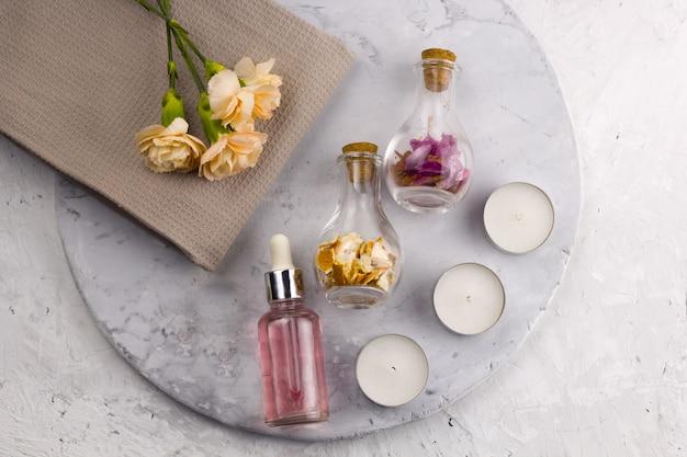 Conjunto de spa, garrafas, velas e flores vista superior fundo de mármore Foto Premium