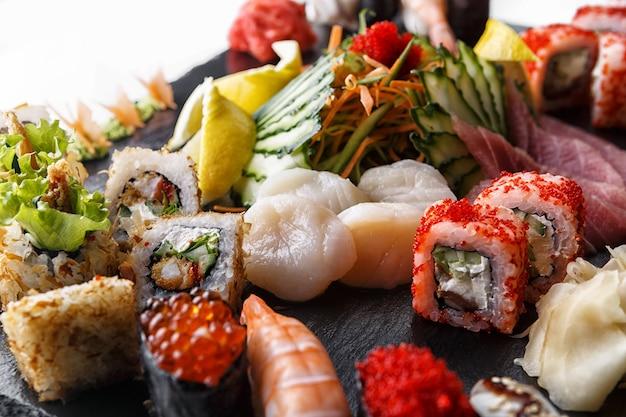 Conjunto de sushi de rolos com vieiras e legumes, em pedra preta Foto Premium