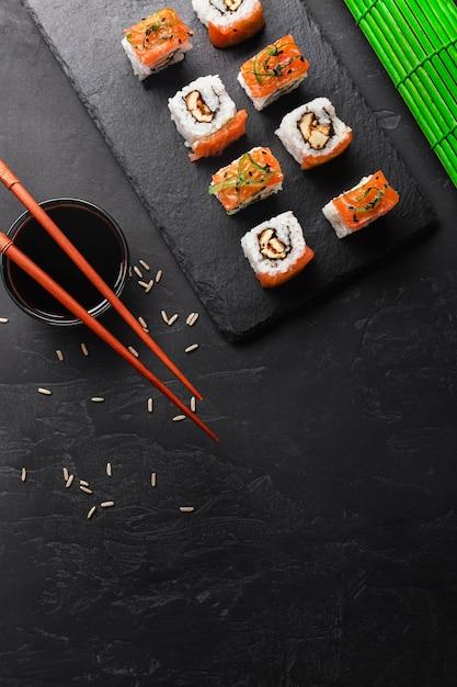 Conjunto de sushi e maki na mesa de pedra. vista superior com espaço para texto Foto Premium
