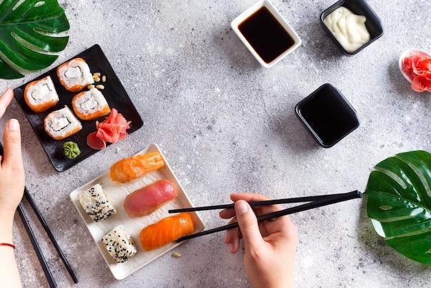 Conjunto de sushi fresco em ardósia preto e branco, mão segure varas de metal, molho e folhas verdes Foto Premium