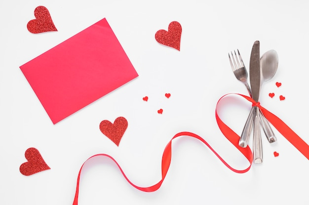 Conjunto de talheres com corações e papel-de-rosa Foto gratuita
