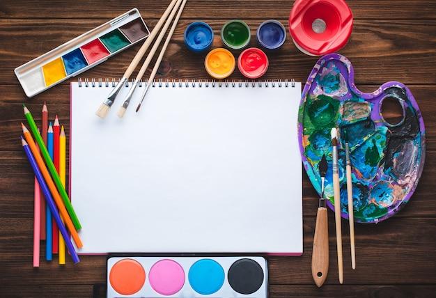 Conjunto de tintas, lápis, ferramentas para pintura e folha de papel branco em branco Foto Premium
