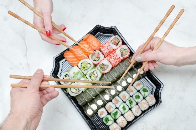 Conjunto de três mãos com pauzinhos e sushi. vista do topo Foto Premium