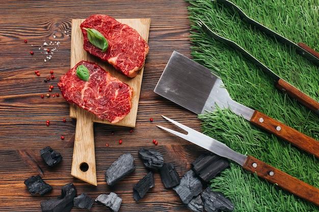 Conjunto de utensílio de churrasco e carvão com bife cru na mesa de madeira Foto gratuita