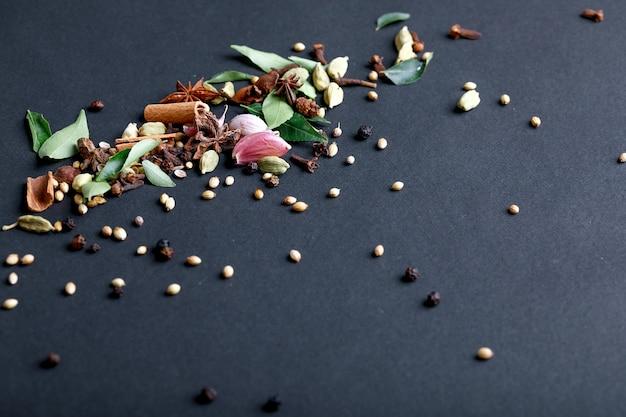 Conjunto de várias especiarias em fundo preto. Foto Premium