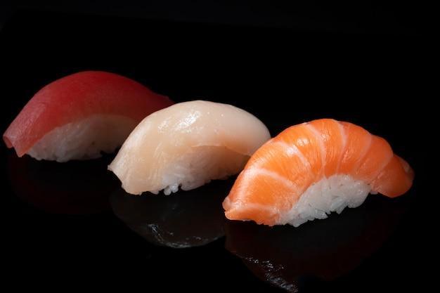 Conjunto de vários sushi nigiri clássico isolado no preto Foto Premium
