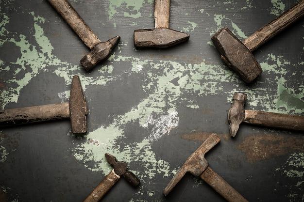 Conjunto de velhos martelos e pregos enferrujados. ferramentas em metal a superfície. Foto Premium